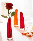 Orange and red glass vases with single rose blossom