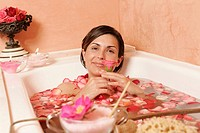 Woman in bath tub with petals holding a flower