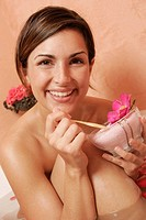 Woman with a bowl with bath salts and petals
