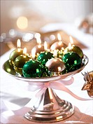 Glossy Christmas tree ball candles in a silver bowl