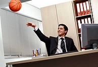 Office worker at desk playing with a basketball