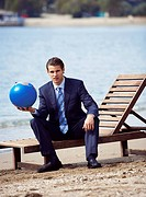 Businessman on chaise lounge with globe (thumbnail)