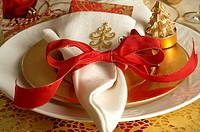 Christmas table place setting, napkin and a red ribbon