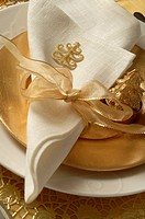 Christmas table place setting, napkin tied with a golden ribbon