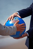 Businessmen's hands grasping globe (thumbnail)