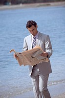 Businessman on beach reading a newspaper (thumbnail)