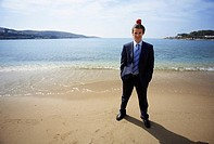 Businessman on beach with apple balanced on his head