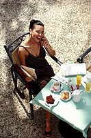 Businesswoman having breakfast in garden cafe