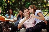 Woman sitting on man's lap in outdoor cafe (thumbnail)