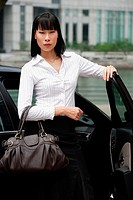 Businesswoman with hand on car door, carrying bag, looking at camera