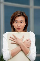 Female executive hugging folders, sad expression