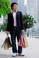 Man standing with shopping bags, looking away