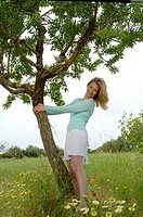 Woman is embracing a tree in a meadow