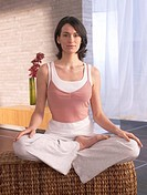 Woman sitting cross-legged doing yoga exercise