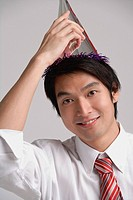 Businessman wearing party hat, looking at camera