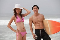 Couple on beach, man carrying surfboard