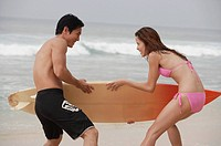 Couple on beach, fighting for surfboard