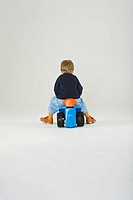 Rear view of a boy riding a tricycle
