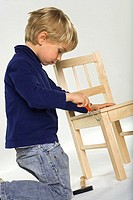 Side profile of a boy repairing a chair