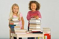 Two girls standing behind stacks of books and smiling