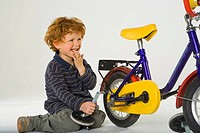 Side profile of a boy holding a wheel trigger of a bicycle and smiling