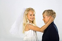 Side profile of a boy with a girl imitating a bride and a groom