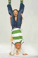Boy doing a handstand with a girl standing behind him and helping him