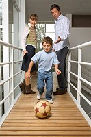 Young boy playing soccer in the house