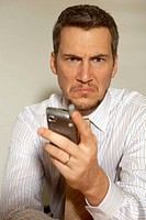 Close-up of a businessman holding a mobile phone and looking frustrated