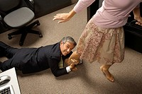 High angle view of a businessman grabbing his colleague´s leg