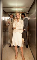 Businesswoman using a mobile phone with two businessmen standing behind her in an elevator