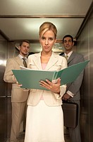 Portrait of a businesswoman holding a file with two businessmen standing behind her in an elevator
