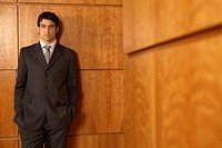 Portrait of a businessman standing and leaning against a wall (thumbnail)