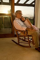 Grandfather and granddaughter in rocking chair