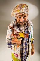 Portrait of a mature man holding a paint roller