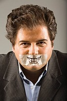 Portrait of a mid adult man with duct tape over his mouth
