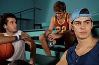 Three young men sitting in a basketball court (thumbnail)