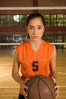 Portrait of a young woman holding a basketball (thumbnail)