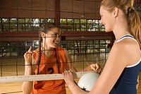 Two young women standing in a volleyball court and smiling