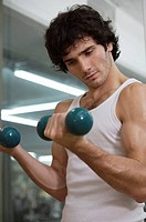 Close-up of a young man exercising with dumbbells