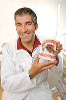 Portrait of a male dentist holding dentures