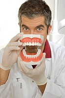 Portrait of a male dentist holding dentures in front of his face