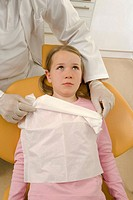 High angle view of a dentist positioning dental bib over a girl
