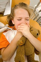 Close-up of a girl with her hands over her mouth in a dentist's office