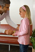 Male doctor giving a gift to a girl