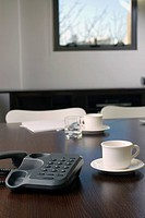 Close-up of a telephone with a tea cup and a saucer on a desk in an office (thumbnail)