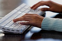 Close-up of a woman's hands typing on a computer keyboard