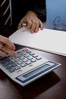 Mid section view of a businessman using a calculator