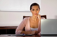 Portrait of a businesswoman sitting in front of a laptop and smirking