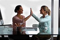 Side profile of two businesswomen giving high-five to each other